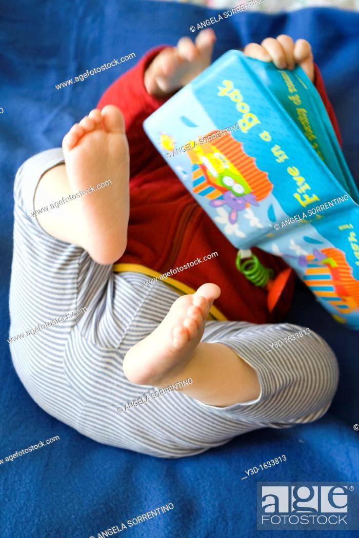Stock Photo: Toddler baby playing with book.