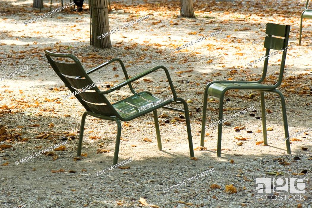 Stock Photo: France, Paris, metal chairs set face to face in park.
