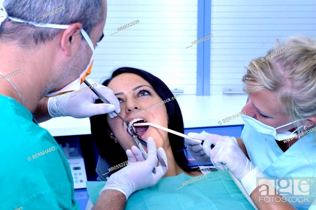 Imagen: female patient at the dentist sitting at the surgery couch - dentist's assistant - extraction of molar tooth.