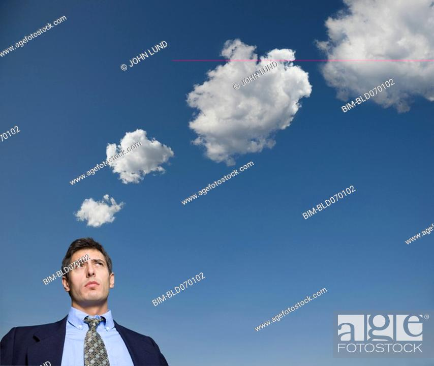 Stock Photo: Hispanic businessman with thought bubbles made of clouds.