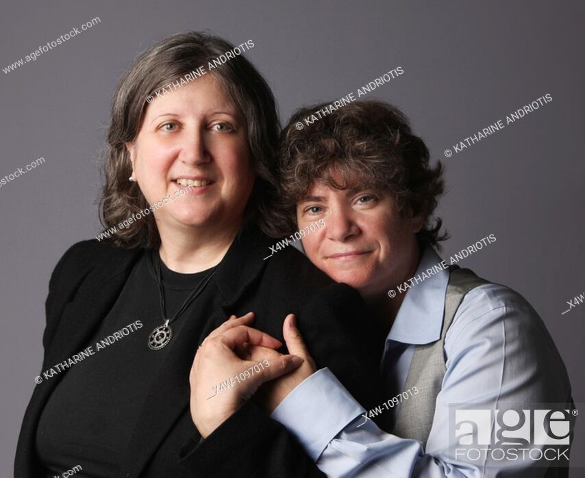 Imagen: Married lesbian couple holding hands and looking at camera.