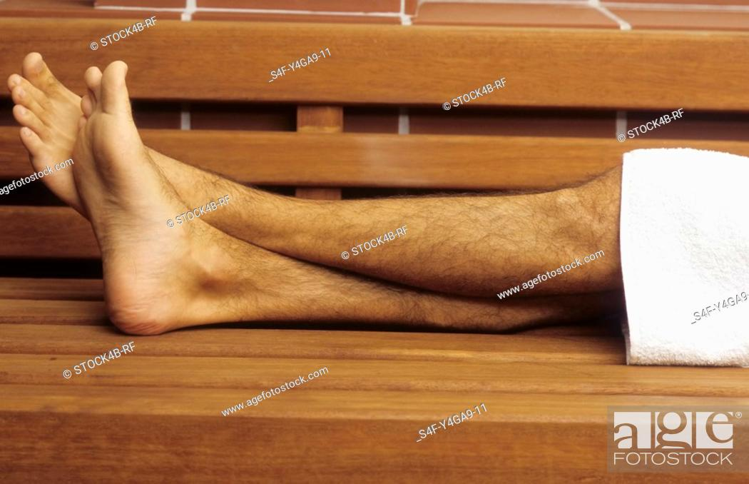 Stock Photo: Naked Legs of a Man with a Towel lying on a wooden Bench - Sauna - Relaxation - Wellness.