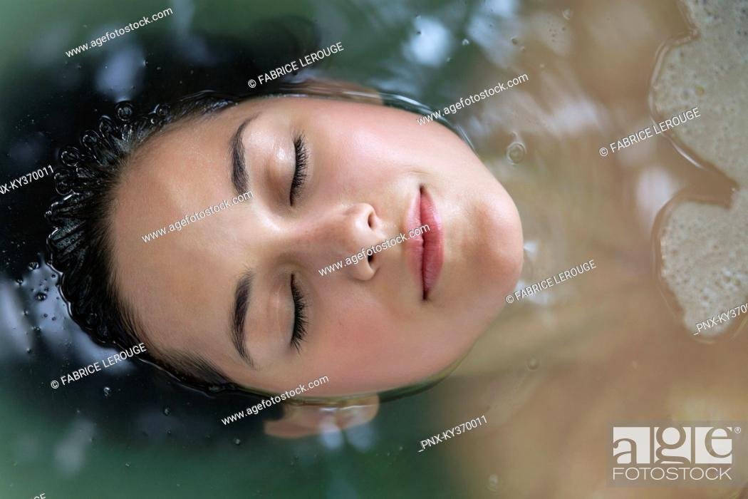 Stock Photo: Beautiful young woman relaxing in a bathtub with her eyes closed.