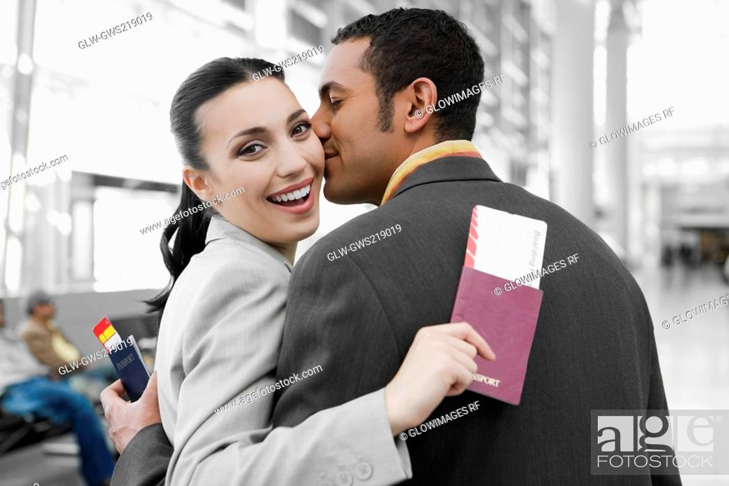 Stock Photo: Close-up of a businessman kissing a businesswoman at an airport.