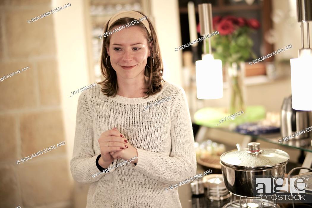 Imagen: woman, pleasant anticipation next to prepared food.