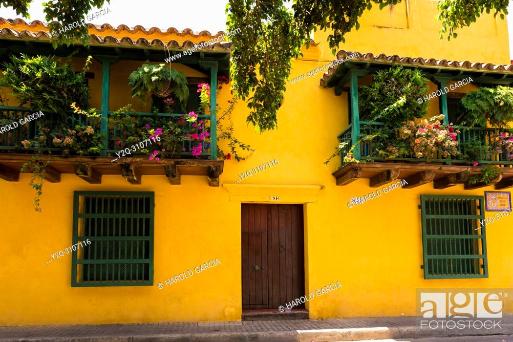 Imagen: Beautiful houses with large doors, big windows and green foliage n the ancient walled city of Cartagena de Indias. Historical patrimony of the humanity for the.