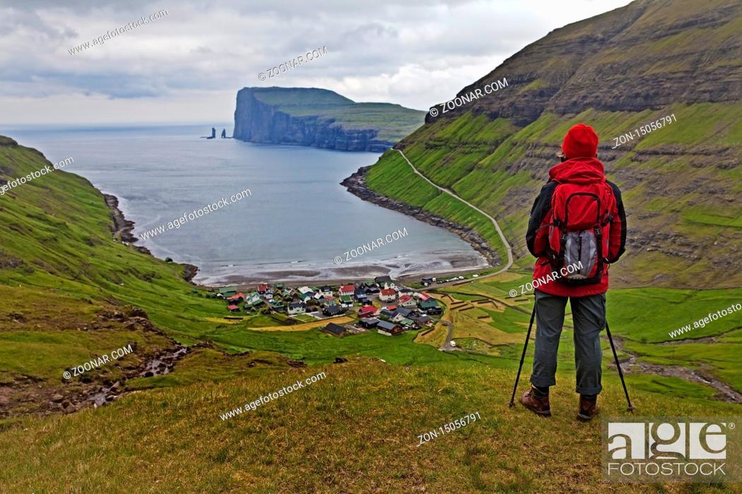 Stock Photo: Eine Wandererin schaut auf den kleinen Ort Tjørnuvík und den Atlantik, Streymoy, Faeroeer, Føroyar, Daenemark, Europa.