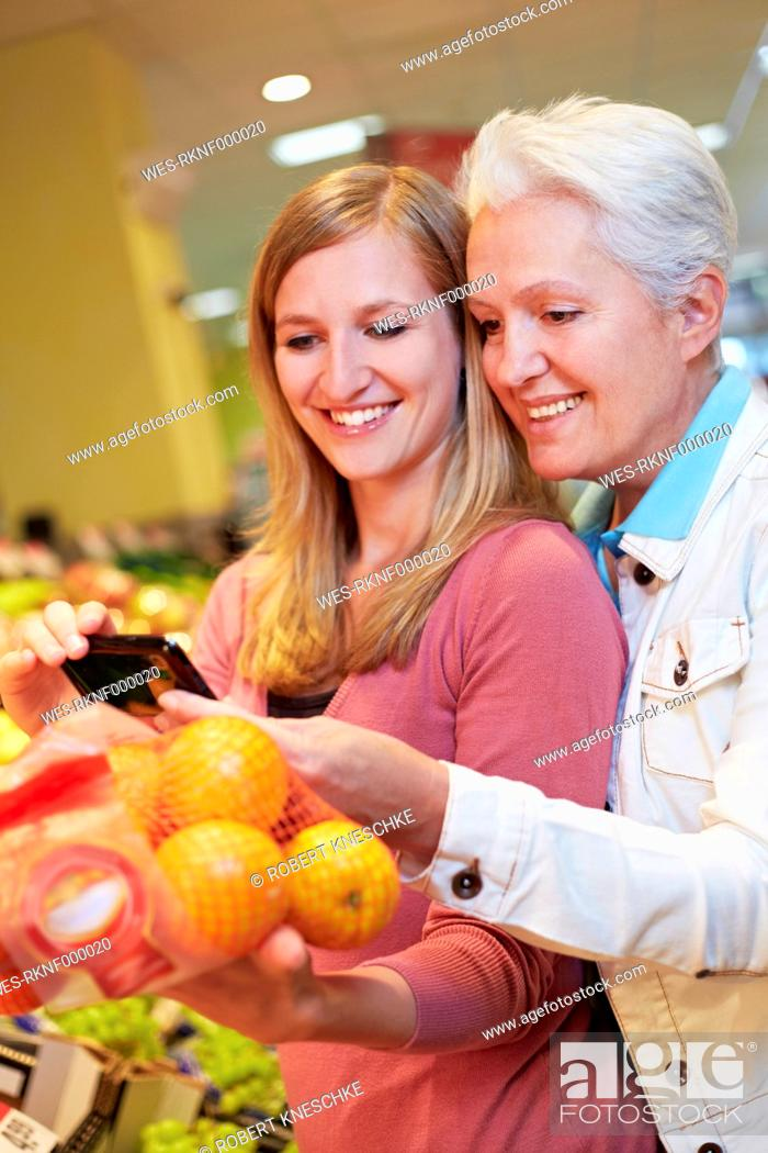 Stock Photo: Germany, Cologne, Womens with smart phone and oranges in supermarket.
