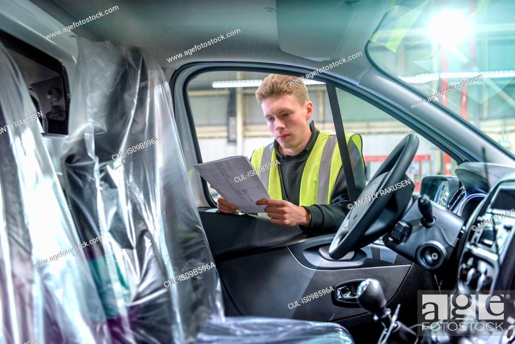 Stock Photo: Apprentice vehicle inspector inspecting interior of vehicle in car factory.