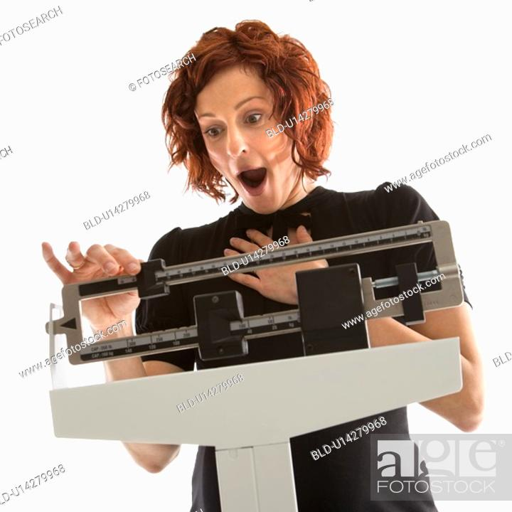 Stock Photo: Pregnant Caucasian mid-adult woman surprised by her weight shown on scale.