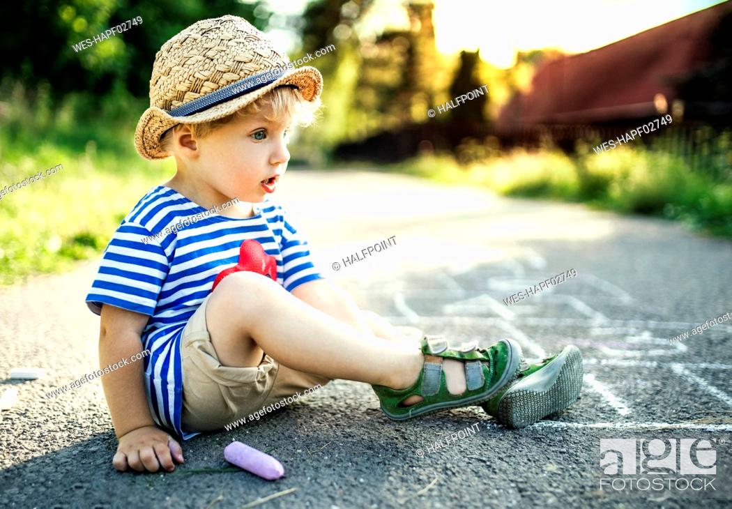 Stock Photo: Daydreaming toddler boy sitting on the street.