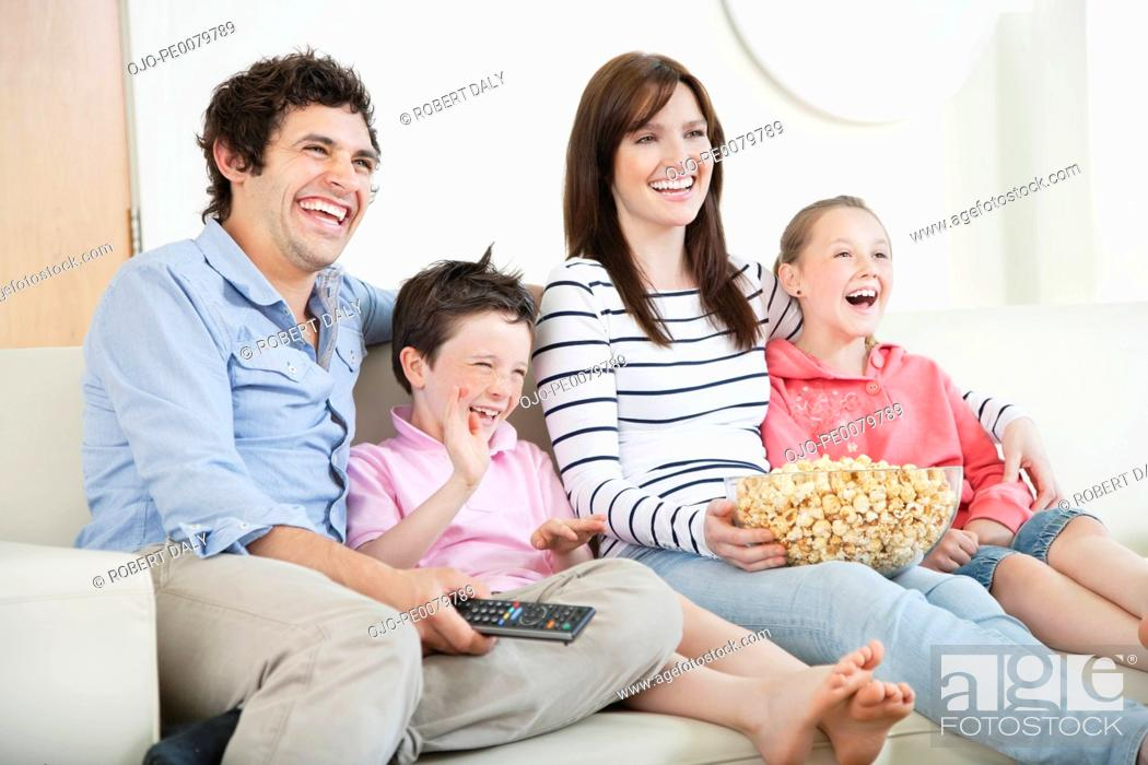 Stock Photo: Happy family with popcorn watching TV on sofa.