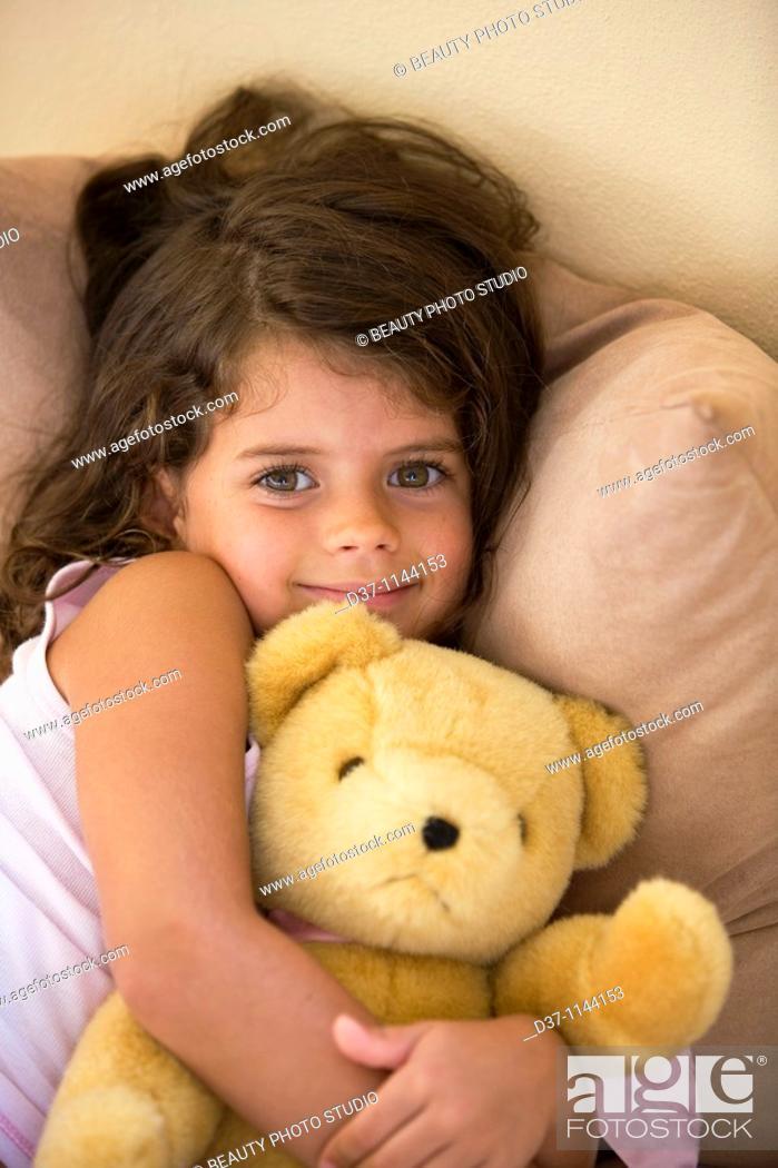 Stock Photo: Caucasian girl hugging her teddy bear.