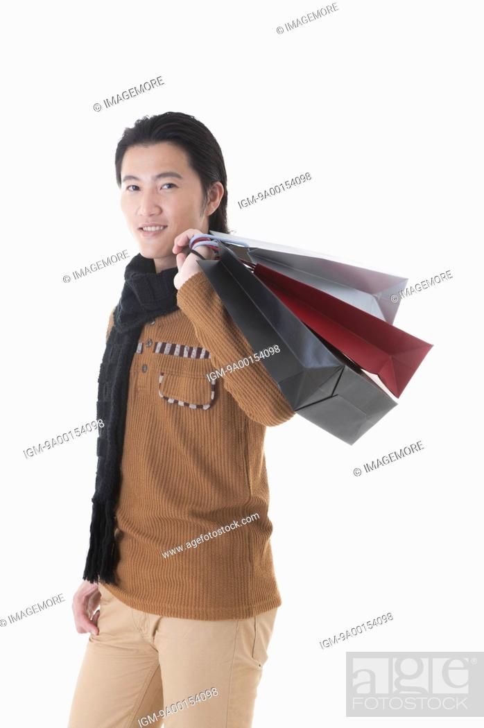 Stock Photo: Mid adult man carrying shopping bags on shoulder.
