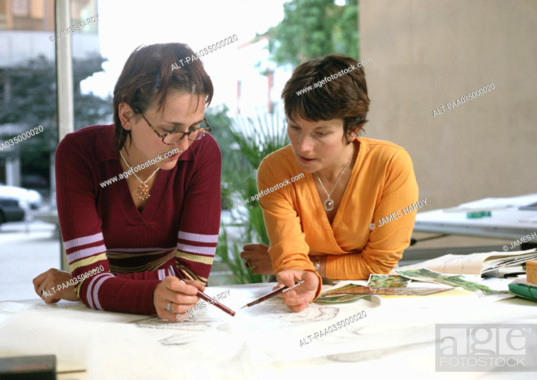 Stock Photo: Two women leaning on table, holding pens.