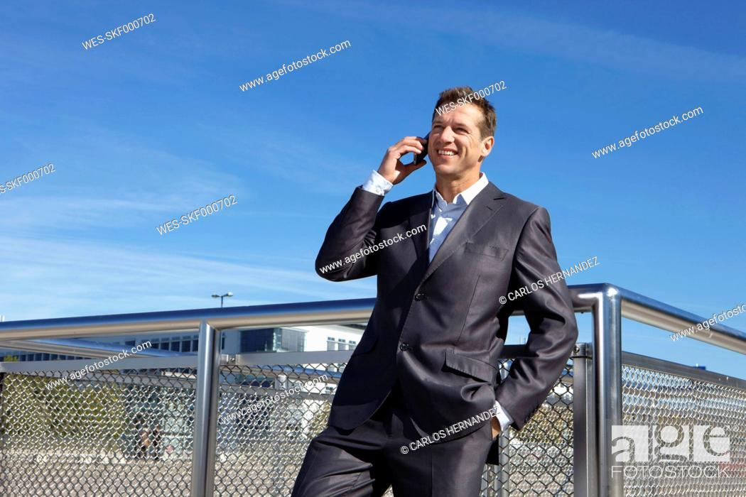 Stock Photo: Germany, Bavaria, Munich,Businessman talking on cell phone, smiling.