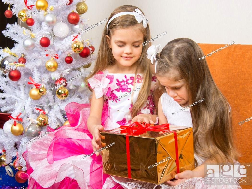 Stock Photo: The older girl gives younger unwanted gift.