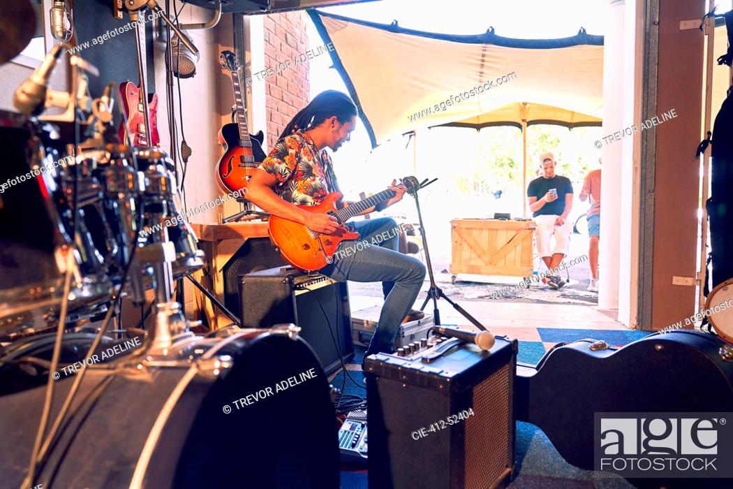 Imagen: Male musician practicing electric guitar in garage recording studio.