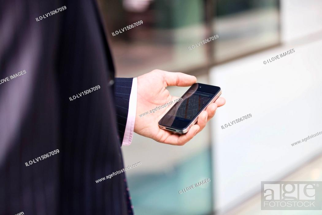 Stock Photo: A businessman looking at a map on his mobile phone.