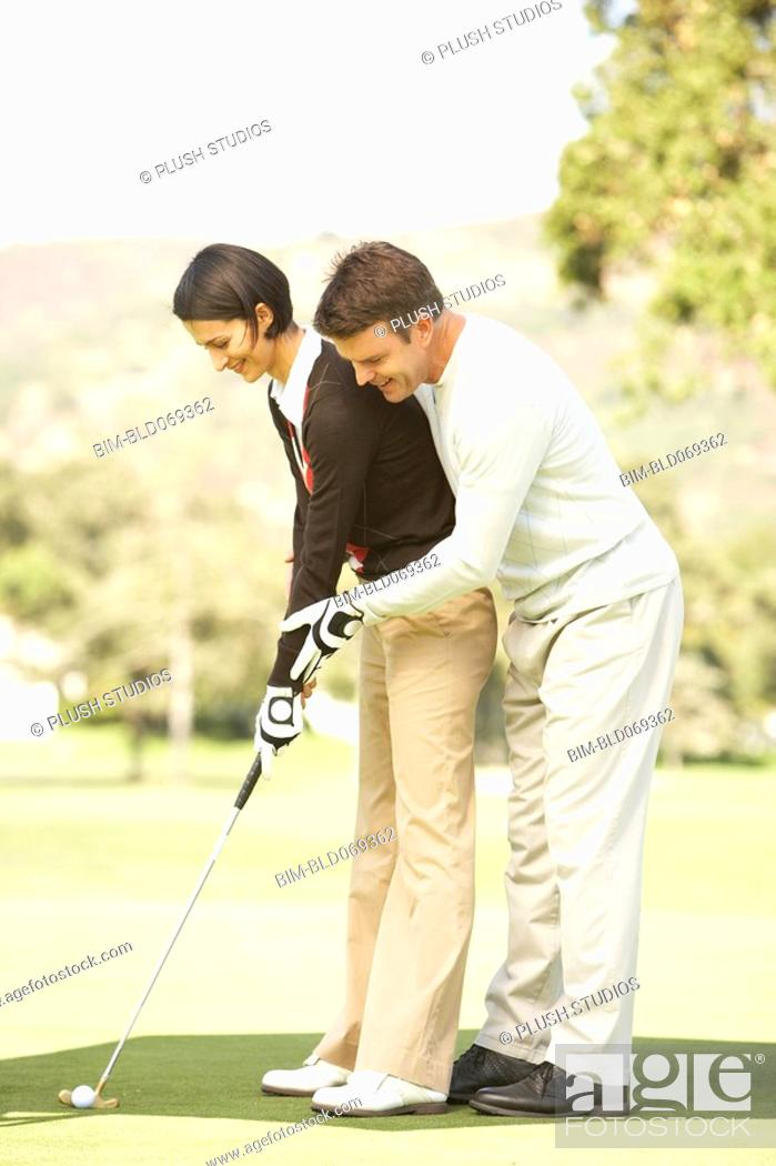 Stock Photo: Man helping wife with golf swing.