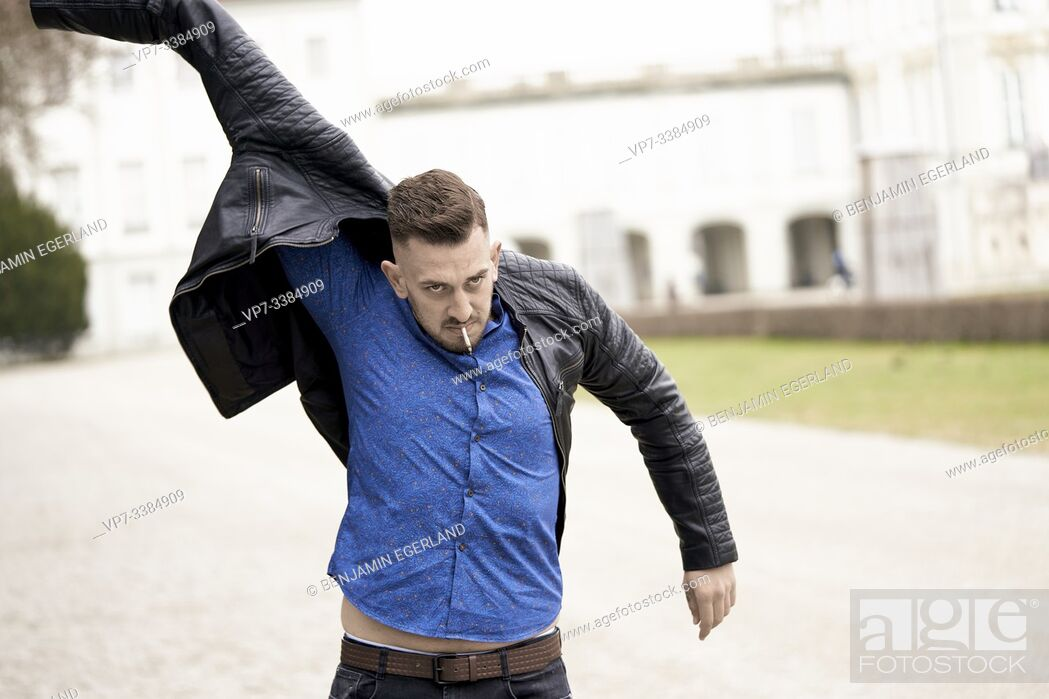 Photo de stock: Man in blue shirt putting on Black leather jacket, Munich, Germany.