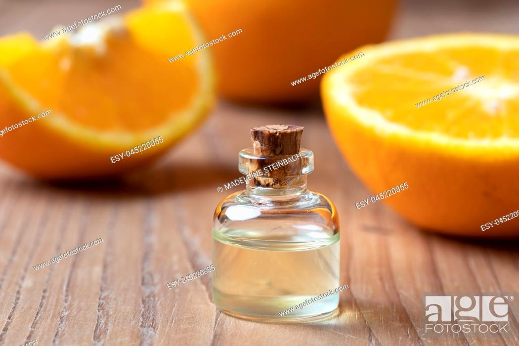 Stock Photo: A bottle of citrus essential oil with fresh oranges in the background.