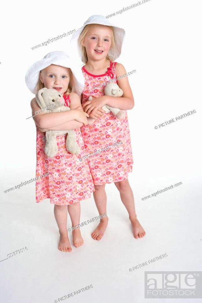 Stock Photo: Portrait of two blond girls with hats and their toy animal.