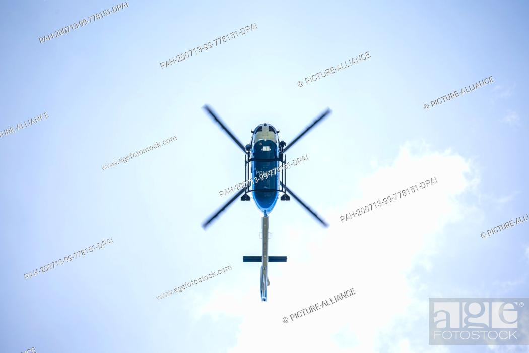 Stock Photo: 13 July 2020, Baden-Wuerttemberg, Oppenau: A police helicopter flies over the region near Oppenau. With a large contingent.