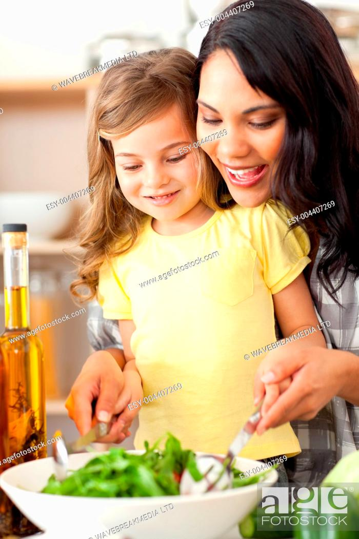 Stock Photo: Brunette mother helping her daughter prepare salad.