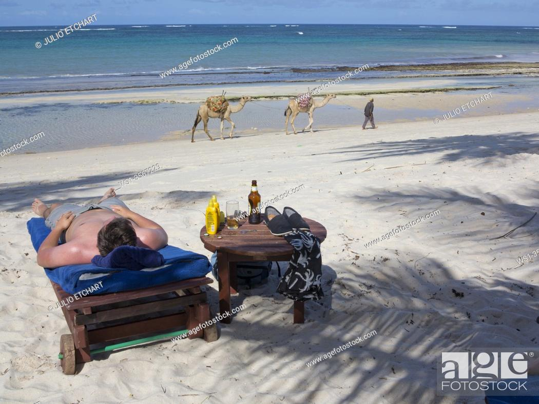 Stock Photo: Tourists sunbathe at holiday resort with local man pulling camels for hire in background on the beach at Tiwi, on Indian Ocean coast, Kenya.