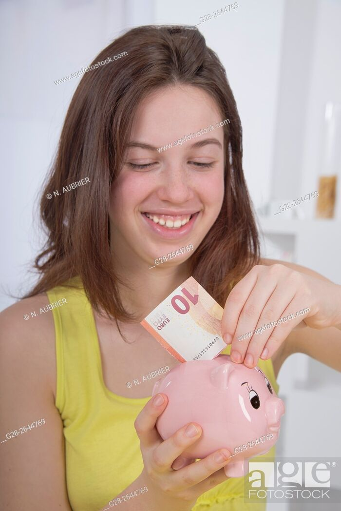 Stock Photo: Smiling teenage girl in yellow putting a 10 euro banknote in her piggy moneybank.