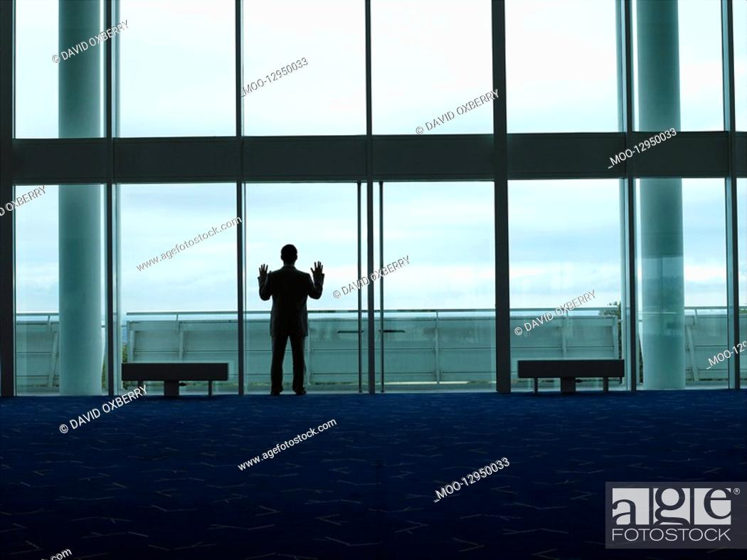 Stock Photo: Businessman standing Looking out Window back view.