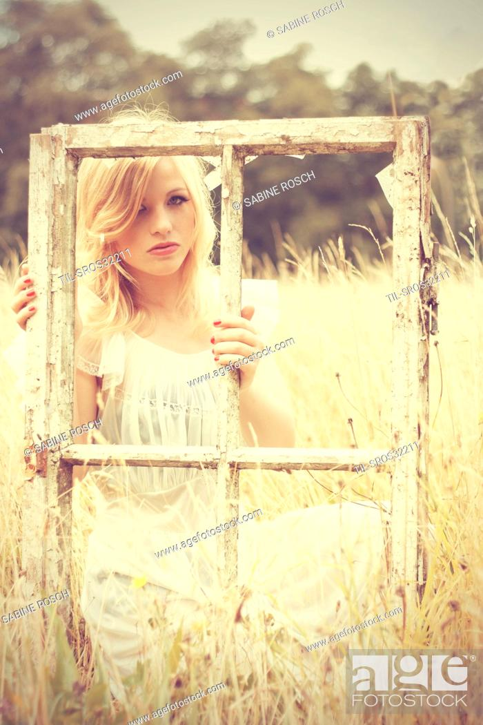 Stock Photo: young woman with blonde hair looking in the camera wearing a white vintage dress and holding an old window in her hands.