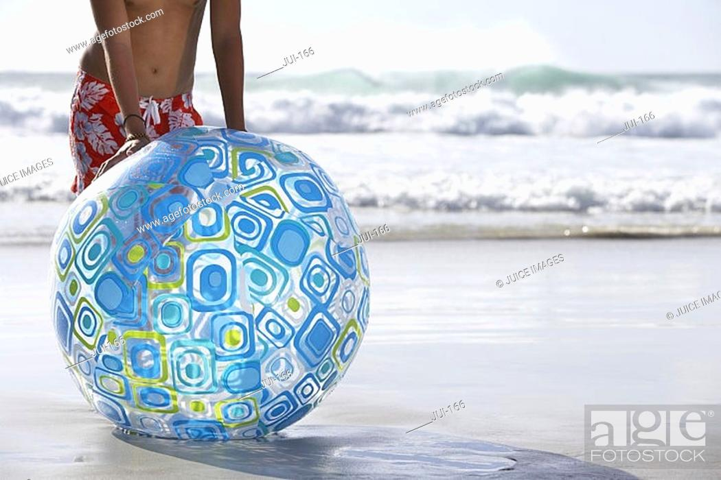 Stock Photo: Teenage boy 13-15 standing on sandy beach behind large blue beach ball, low section.