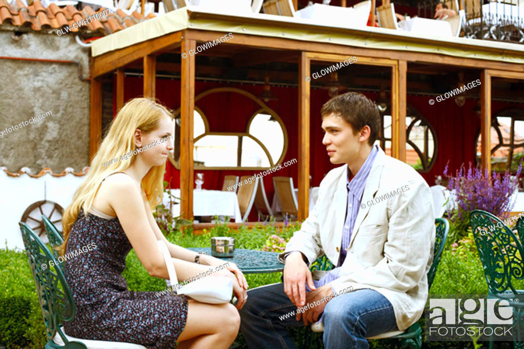 Stock Photo: Young couple sitting together outdoors.