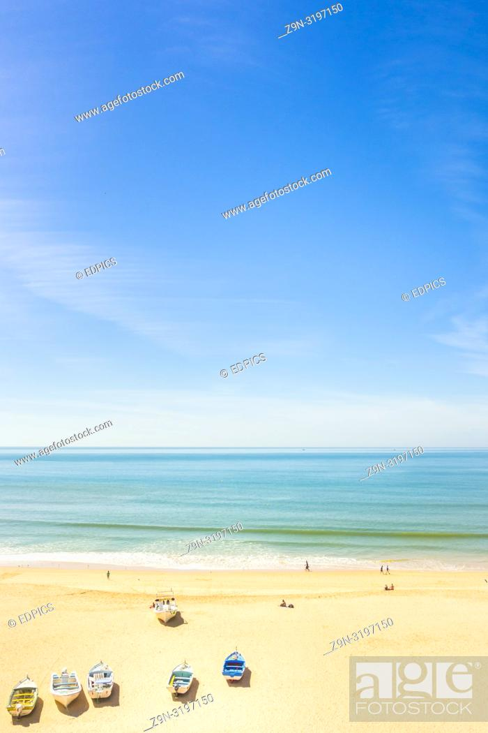 Stock Photo: tourists and fishing boats on the beach of armacao de pera, algarve, portugal.