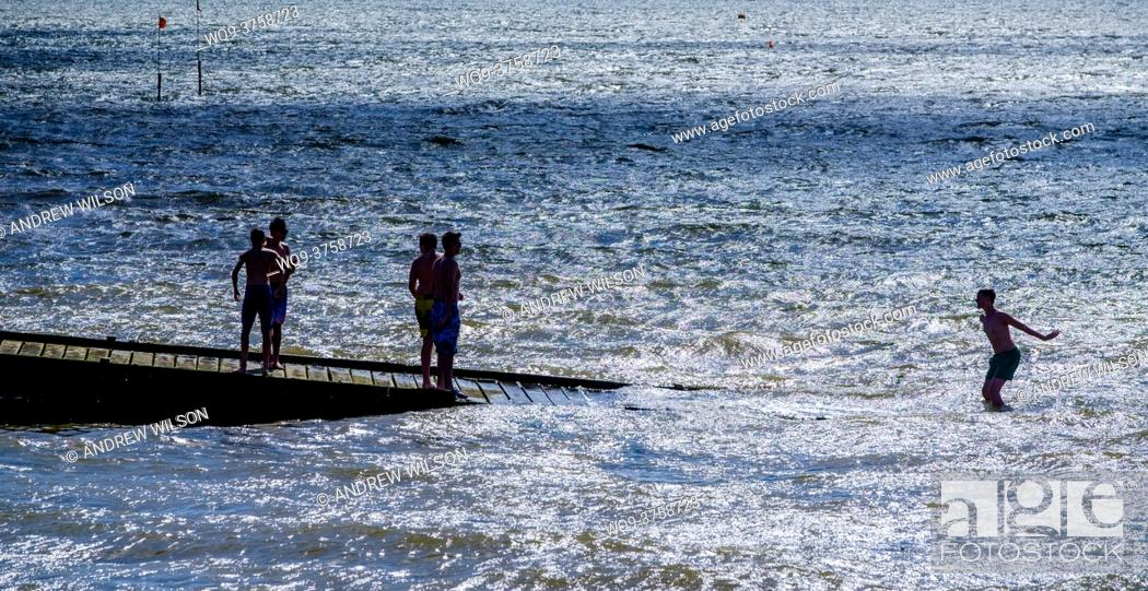 Stock Photo: People playing in the sea off Whitstable, Kent, England.