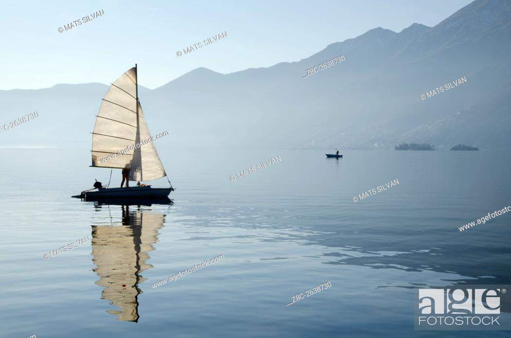 Stock Photo: Sailing boat reflected on alpine lake Maggiore with Brissago islands and mountain in Ascona, Switzerland.