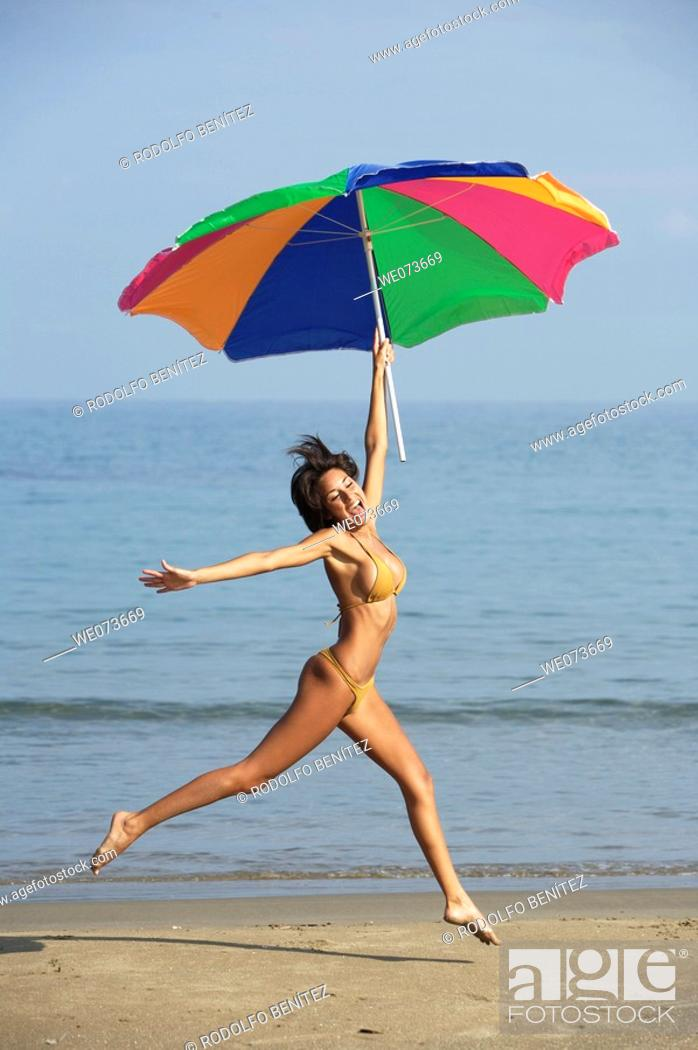 Stock Photo: Latin girl jumping on the beach with an umbrella.
