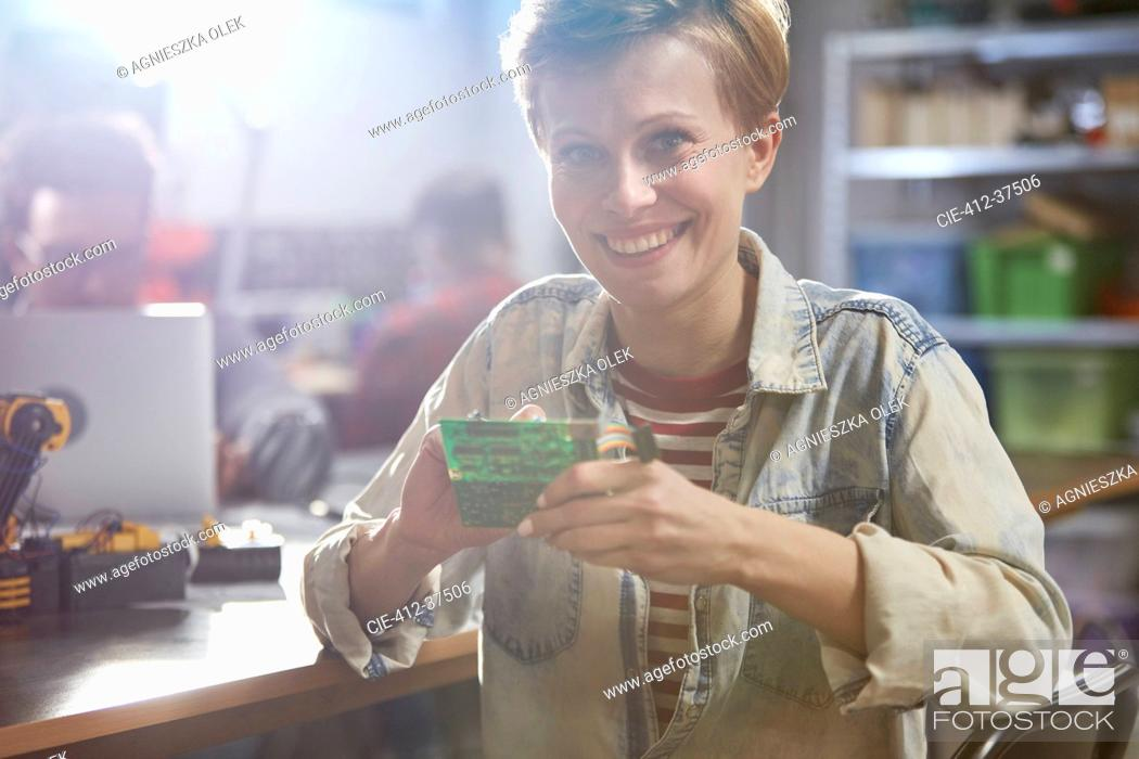 Stock Photo: Portrait smiling female engineer assembling circuit board in workshop.