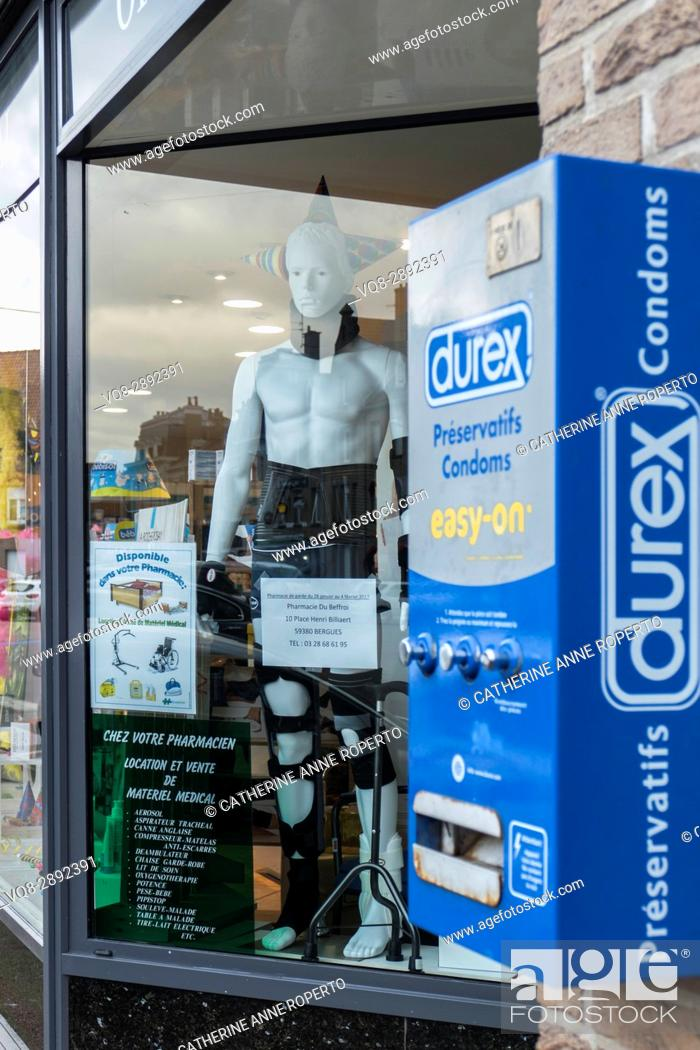 Stock Photo: Rubber clad plastic mannequin next to Durex condom machine in town square pharmacy, Berques, France.