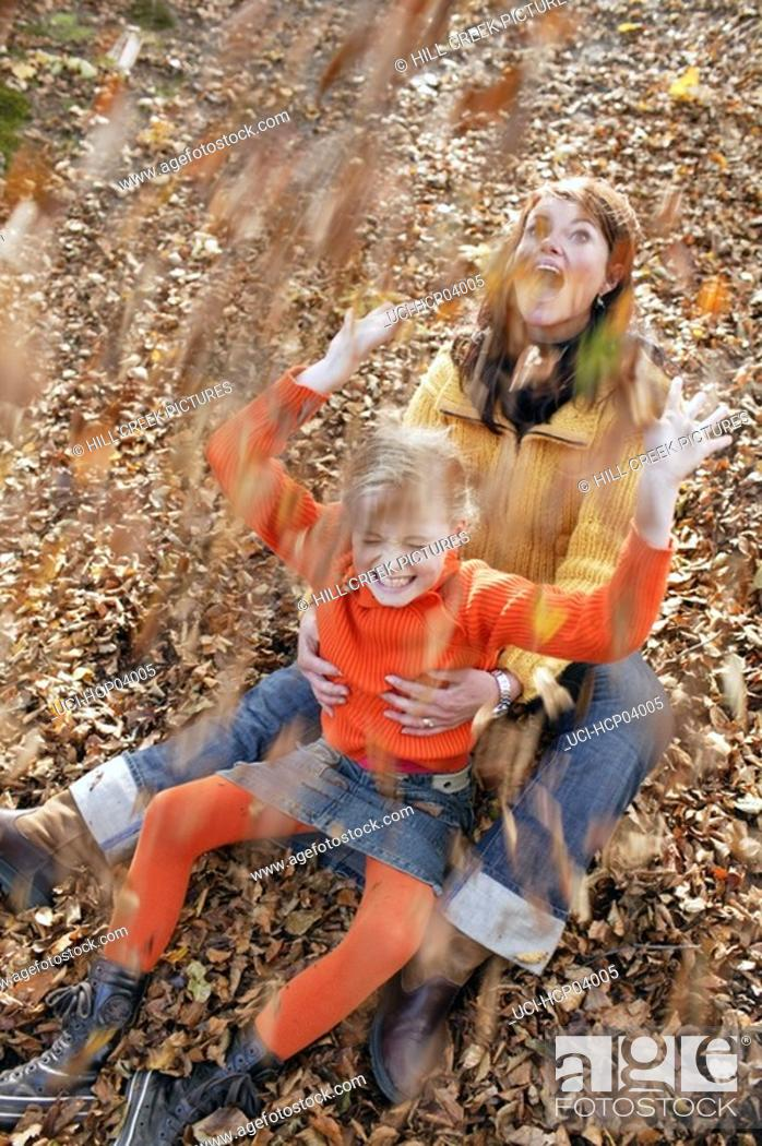 Stock Photo: Mother and daughter throwing leaves.
