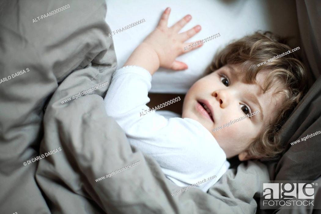 Stock Photo: Toddler boy lying in bed, portrait.