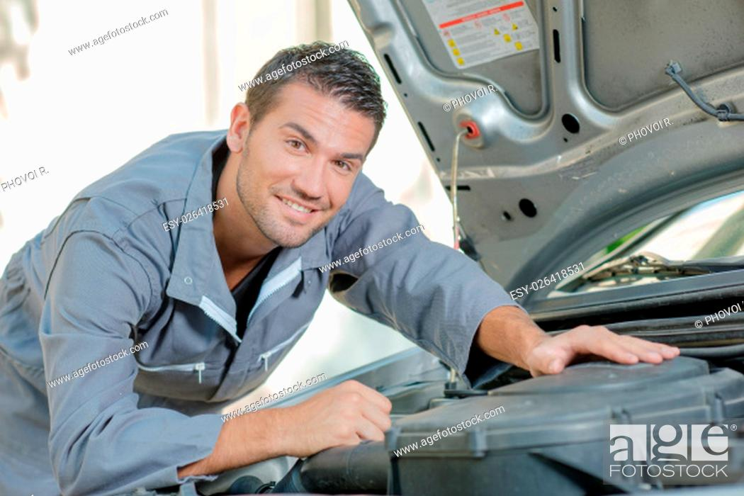 Stock Photo: Mechanic stood by a car.