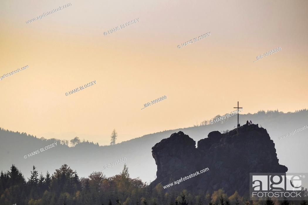 Imagen: Bruchhauser Steine rocks with a group of visitors at the summit cross, backlit, Olsberg, Sauerland, North Rhine-Westphalia, Germany.
