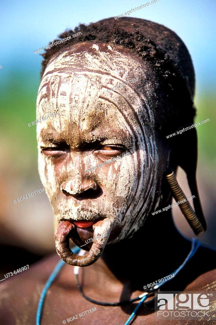 Stock Photo: This woman took her plate out of her lower lip. the white ash color covers the face in order to scare rival tribals.