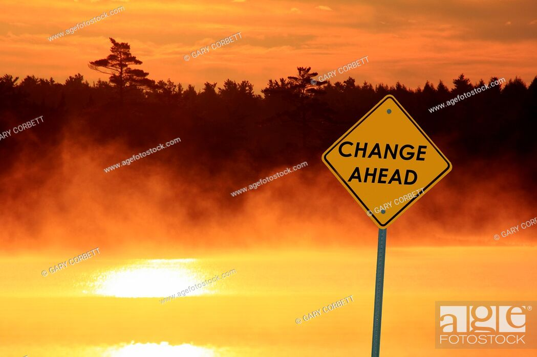 Stock Photo: a caution sign beside a lake at sunrise that says CHANGE AHEAD.