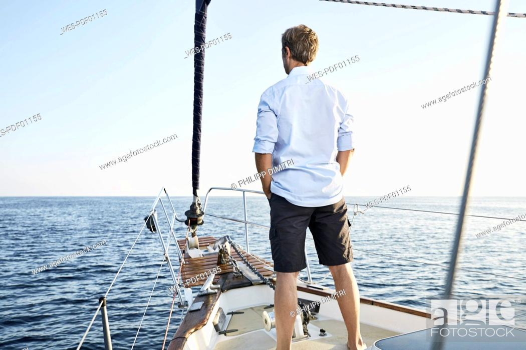 Photo de stock: Back view of mature man standing on his sailing boat looking at distance.