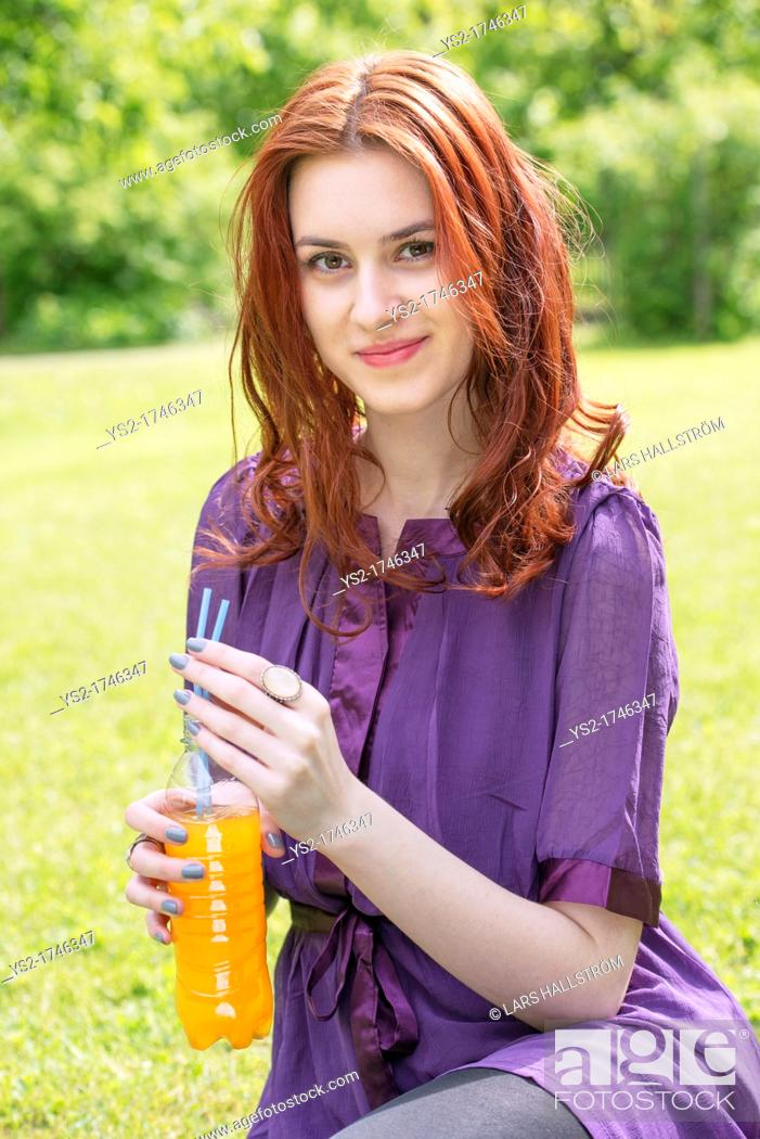 Stock Photo: Portrait of a young woman sitting in a park with a bottle of orange soda.
