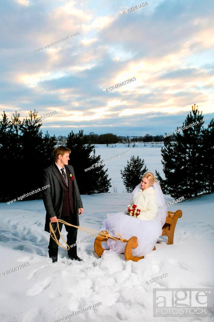 Stock Photo: Winter wedding and beautiful young couple with big wooden sled at the background of snow and cloudy sky.